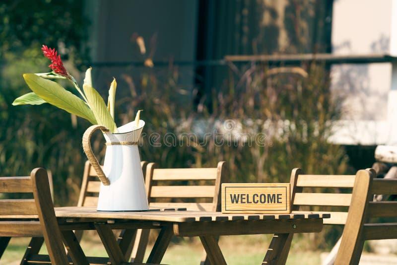 Welkom teken Gezet op een houten lijst met een stoel in het midden van het gazon Verfraaid met uitstekende bloemvazen het gebruik royalty-vrije stock afbeeldingen