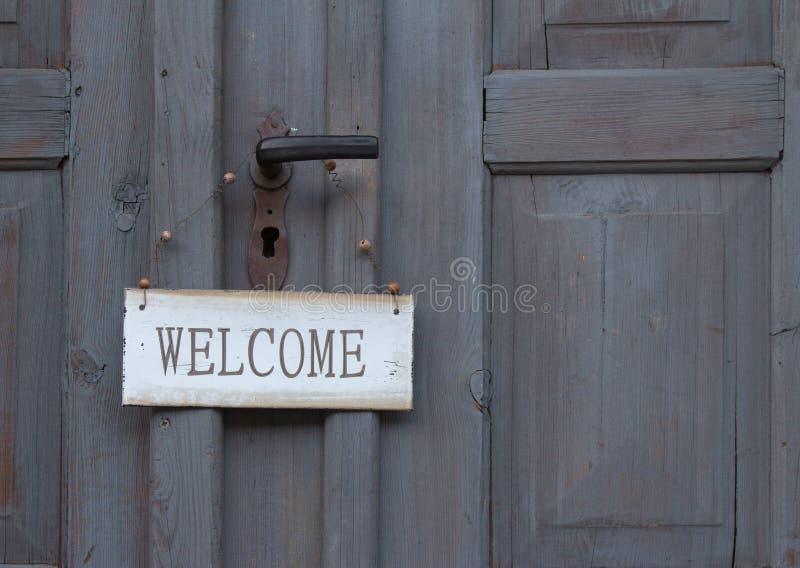 Welkom teken het hangen op een oude houten deur royalty-vrije stock foto