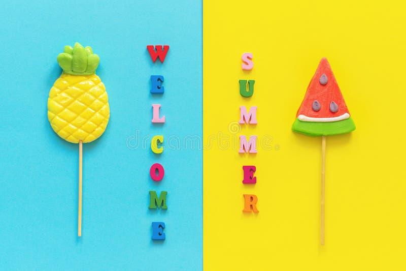 Welkom van de van de de zomer kleurrijke tekst, ananas en watermeloen lollys op stok op blauwe gele achtergrond Conceptenvakantie royalty-vrije stock foto's