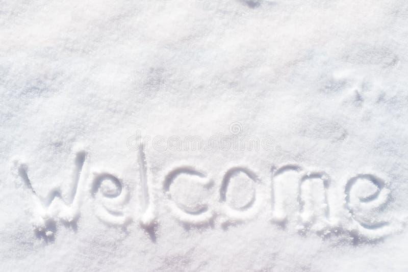 Welkomwoord in de sneeuw op een zonnige dag wordt geschreven die royalty-vrije stock foto