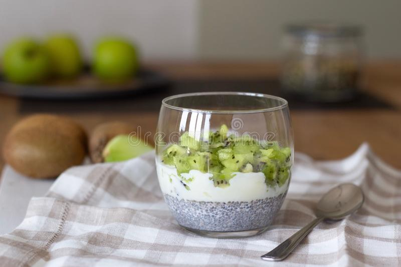 Well being and weight loss concept, healthy vegetarian fruit dessert with kiwi yogurt and chia seeds pudding in a glass, summer royalty free stock photos