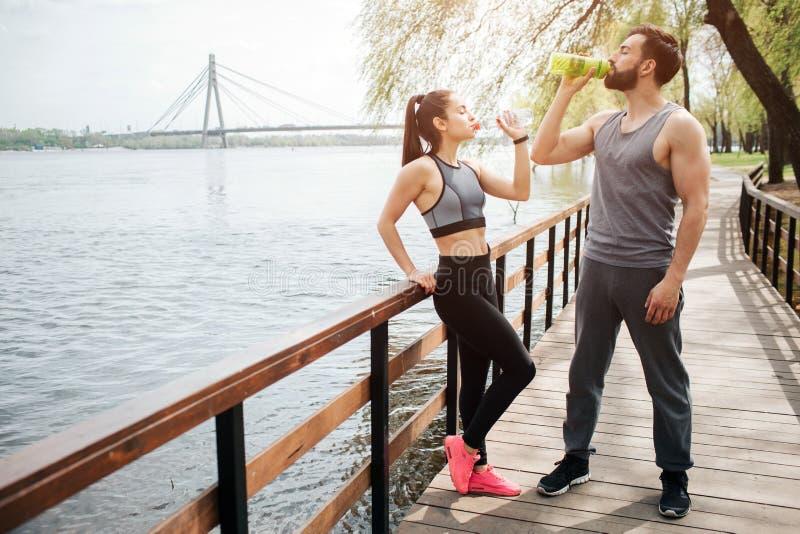 Well-built en mooie mensen ontspannen en hebben een onderbreking Zij zijn drinkwater De man en de vrouw bevinden zich  royalty-vrije stock foto