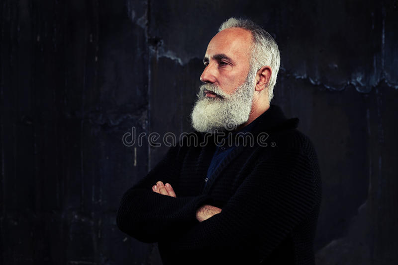 A well-built man with grey beard standing and folded arms looking narrowly. A mid shot from the side of a well-built man with grey beard and folded arms looking stock photos