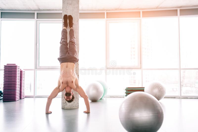 Well-built man is standing on his hands and balancing. He is in the fitness room. stock photography
