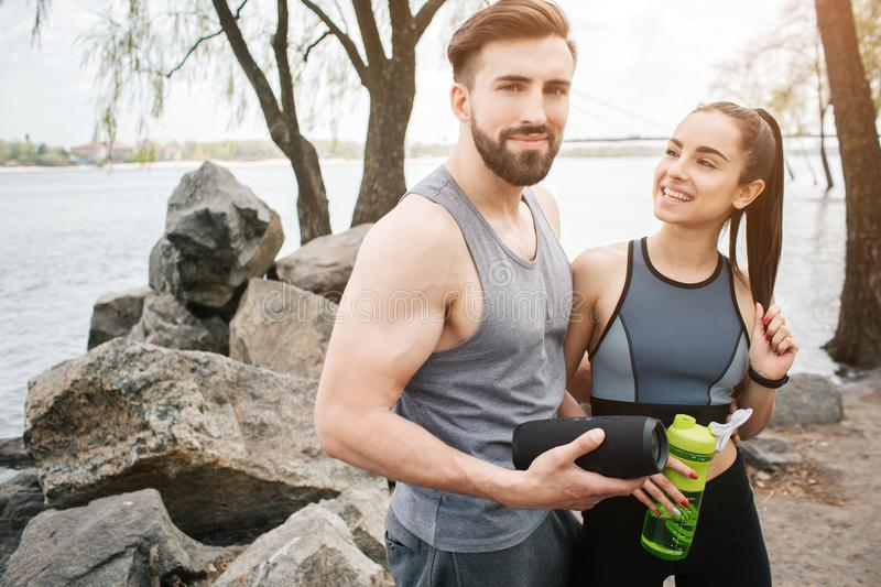 Well-built and slim guy is looking to the camera. He is holsing an amplifier in his hands. Girl is looking at him and stock photography