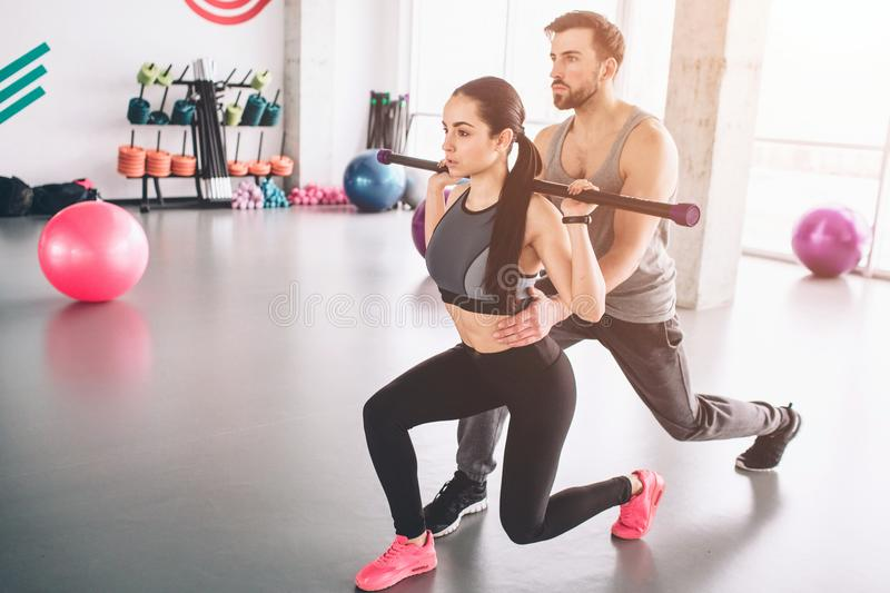 Well-built and strong trainer ih helping beautiful and slim girl to do some attacks carrying bodybar on her shoulders royalty free stock image