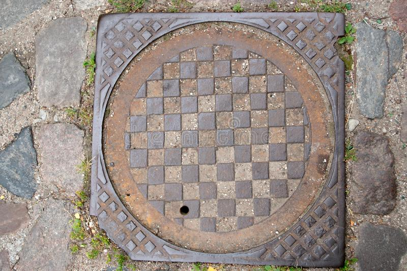 The well of the city drainage sewer with a metal corrugated brown lid with a chessboard pattern, among the gray stones of the pave. The well of the city drainage royalty free stock photo