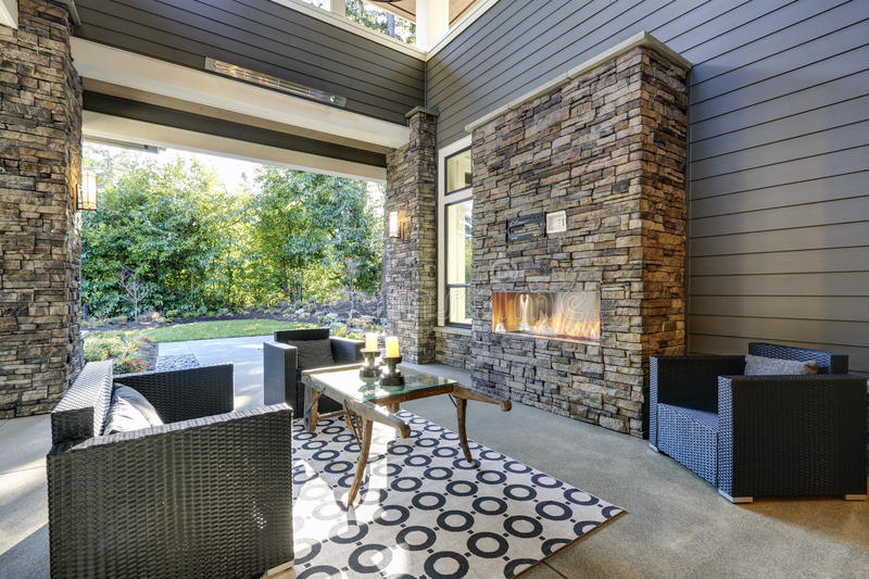 Well designed covered patio boasts stone fireplace. Wicker patio chairs facing gorgeous rustic wood coffee table atop white and black geometric rug. Northwest stock images