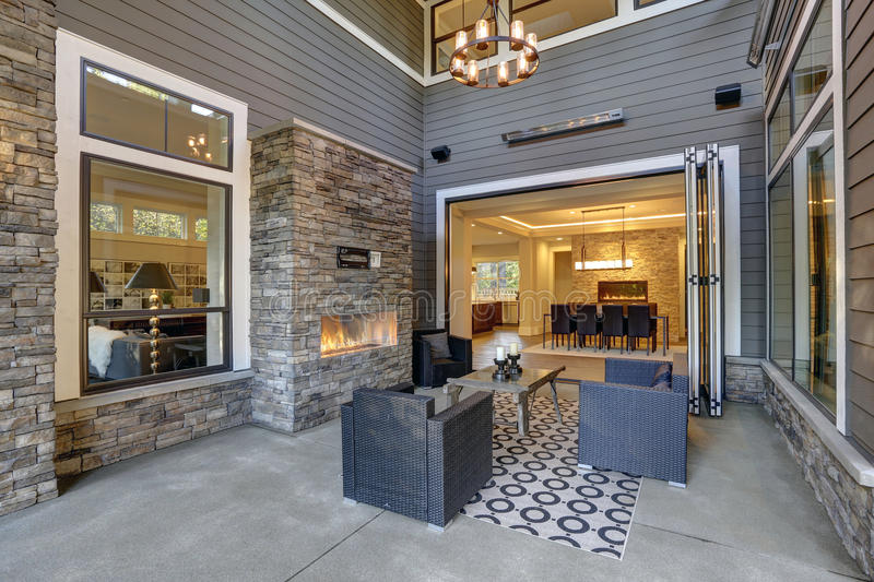 Well designed covered patio boasts stone fireplace. Wicker patio chairs facing gorgeous rustic wood coffee table atop white and black geometric rug. Northwest royalty free stock images