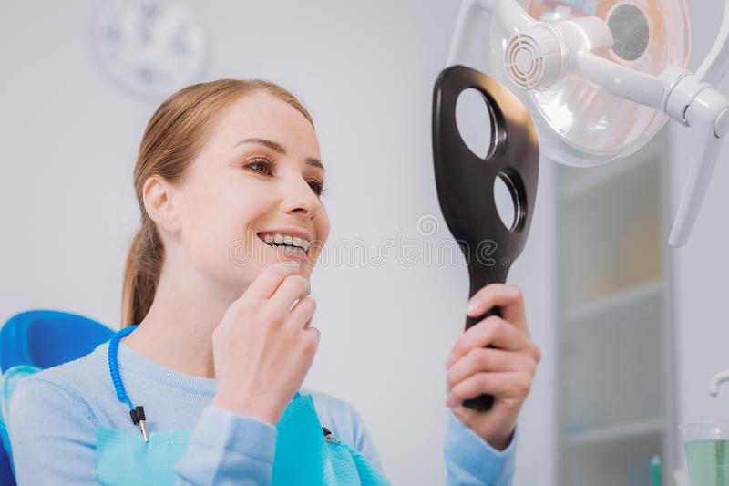 Positive woman holding a mirror while looking at her teeth. Well done. Cheerful young woman visiting a dental clinic and smiling while holding a mirror and royalty free stock photo