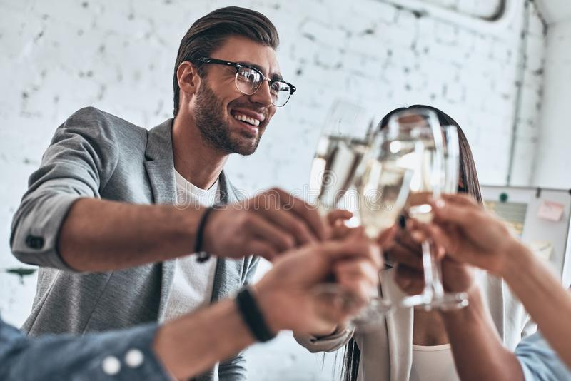Well done everybody. Group of young business people toasting each other and smiling while standing in the board room royalty free stock images