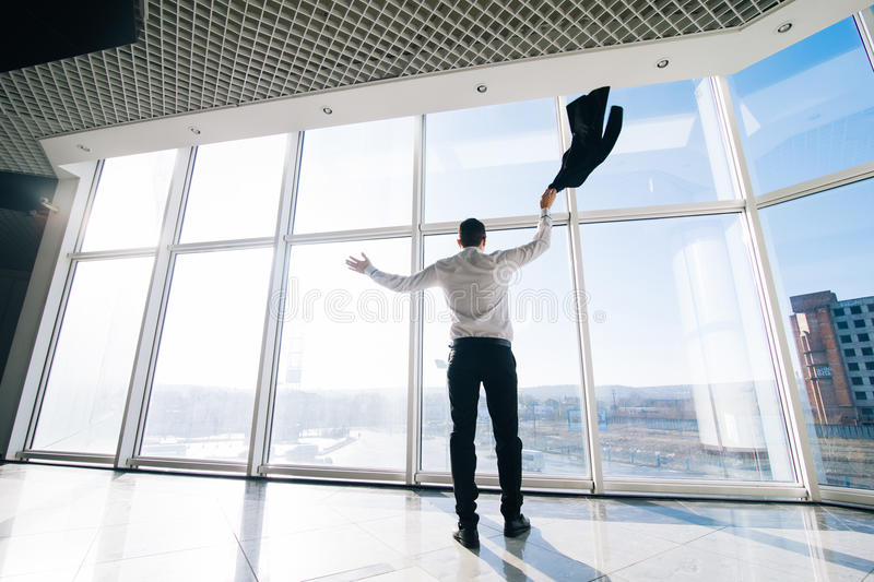 Well done job! Happy manager celebrate win or good deal with raised hands and up jacket. Over panoramic windows royalty free stock image