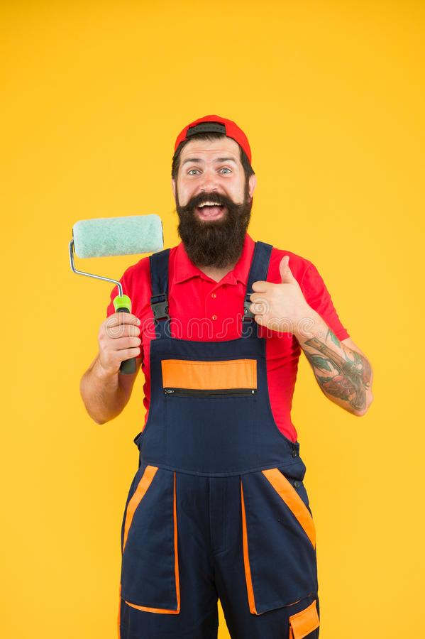Well done. repair success. bearded man worker with roller tool. hipster builder in cap yellow background. erector royalty free stock images