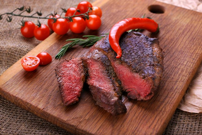 Well-done steak with chili pepper and cherry tomatoes on a wooden dish. Food photo for restaurant menu royalty free stock image