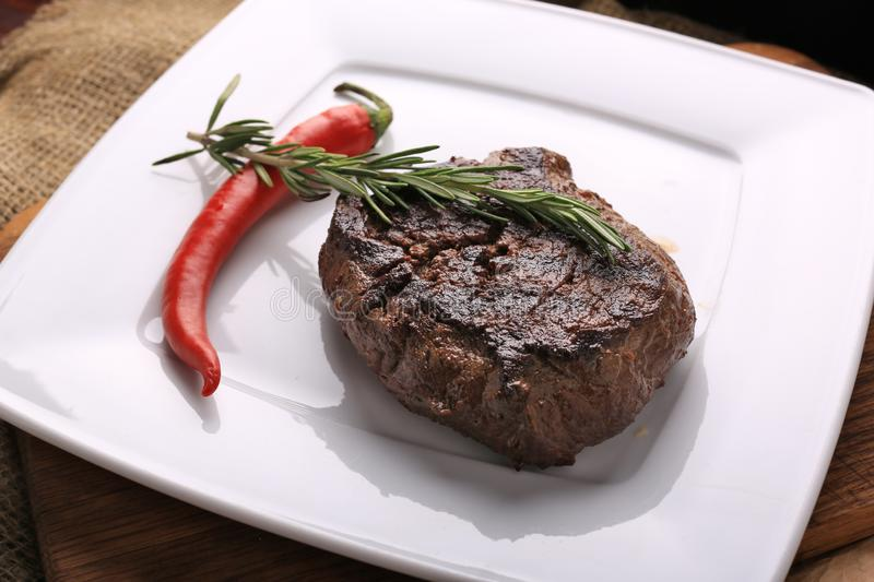 Well-done steak with chili pepper on a white plate. Food photo for restaurant menu stock photo
