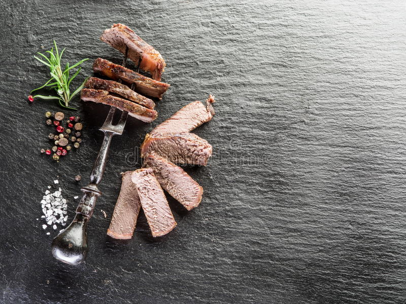 Well-done steak Ribeye. Steak Ribeye with spices on the graphite board royalty free stock image