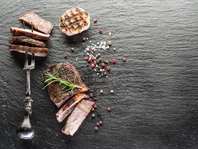 Well-done steak Ribeye. Steak Ribeye with spices on the graphite tray stock photos