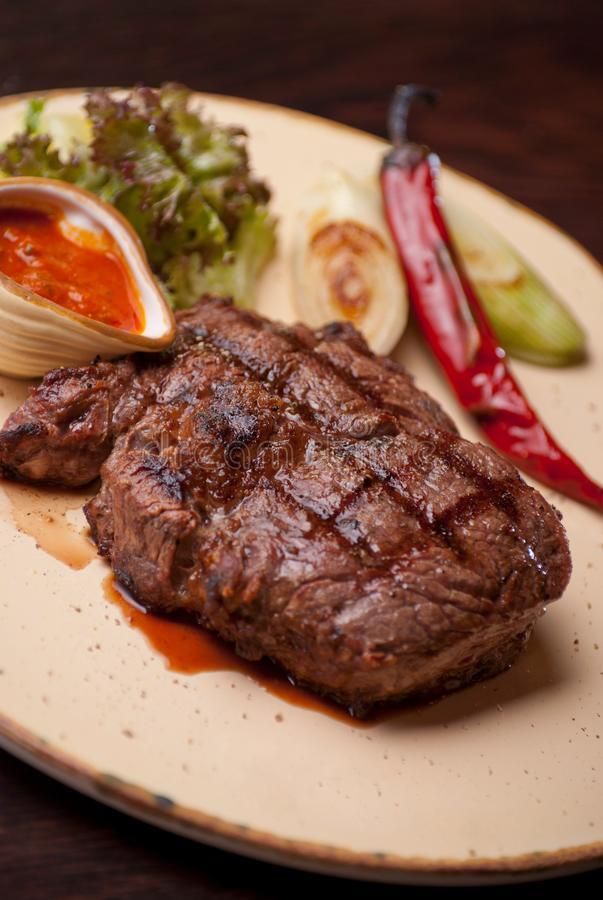 Well-done steak with suace and vagetables. Food photo for restaurant menu royalty free stock photos