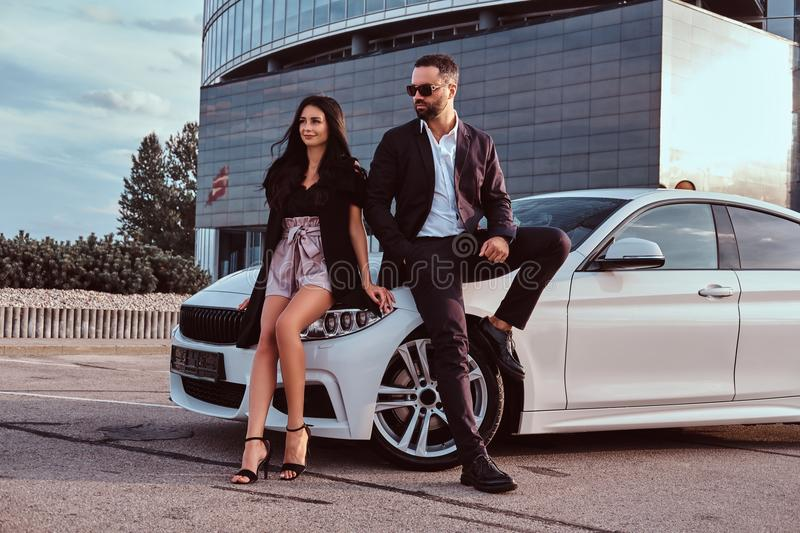 Well-dressed attractive couple leaning on a luxury car outdoors against the skyscraper. Well-dressed attractive couple leaning on a luxury car outdoors against stock photos