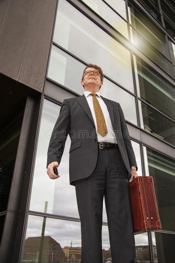 Well dressed businessman with briefcase standing talking on the phone in front of modern glass building  with sun reflection. Pers. On seen from below in frog`s royalty free stock photo