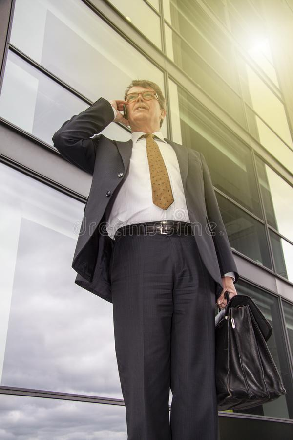 Well dressed businessman with briefcase standing talking on the phone in front of modern glass building  with sun reflection. Pers. On seen from below in frog`s royalty free stock photos