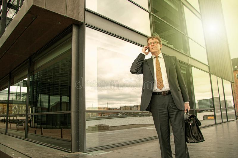 Well dressed businessman with briefcase standing talking on the phone in front of modern glass building  with sun reflection. Pers. On seen from below in frog`s royalty free stock images