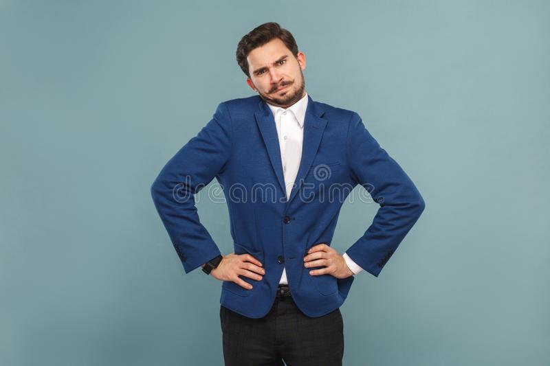 Well dressed confused man standing and looking at camera stock image