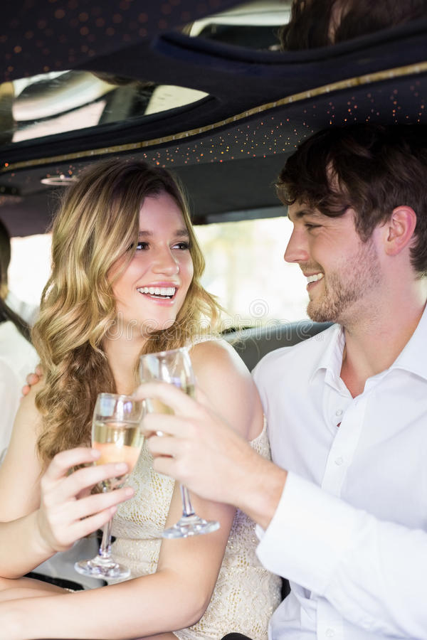 Well dressed couple drinking champagne in a limousine stock image