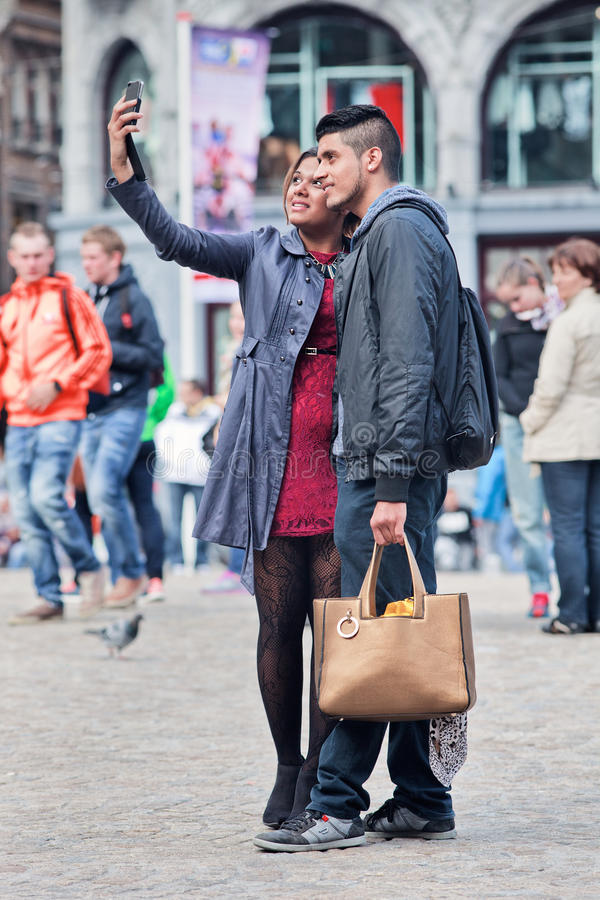 Well dressed couple takes selfie on Dam Square, Amsterdam, Netherlands. AMSTERDAM-AUGUST 26, 2014. Well dressed couple takes selfie on Dam Square. The city is a royalty free stock photos