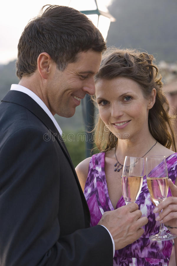 Well-dressed couple toasting champagne flutes royalty free stock photography