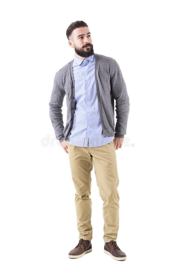 Well dressed man fashion model in gray cardigan looking up with hands in back pockets. royalty free stock photography