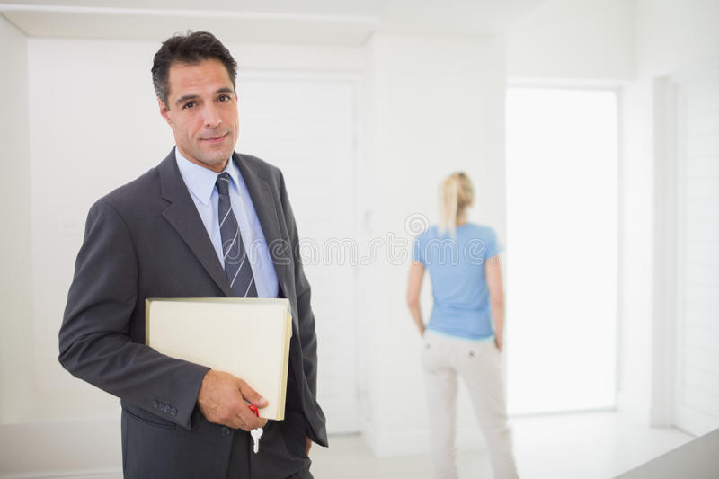 Well dressed real estate agent with blurred woman in background. Portrait of a well dressed real estate agent with blurred women in the background stock images