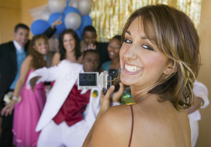 Well-dressed teenager girl video taping friends at school dance stock images