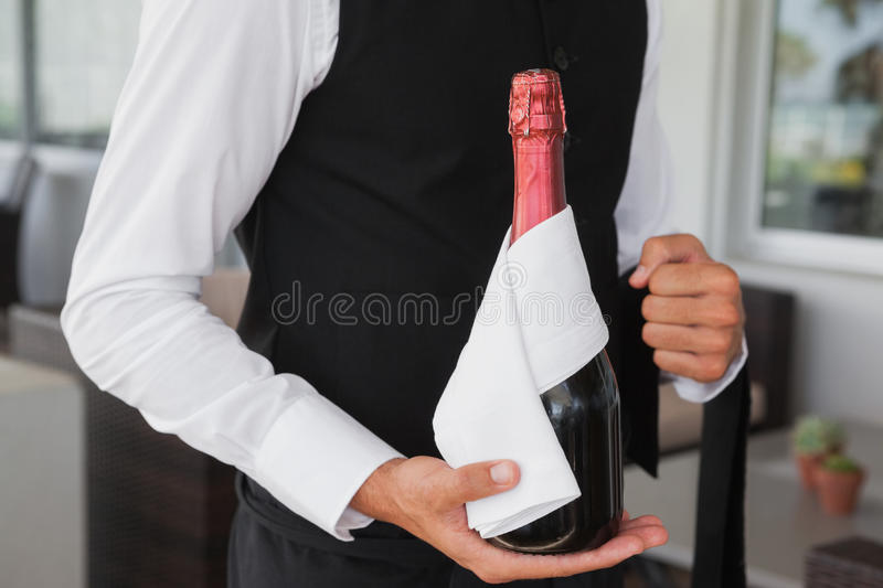 Well dressed waiter holding magnum of champagne royalty free stock photography