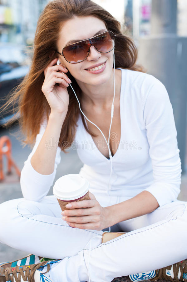 Well dressed woman drinking coffee and listening to the music royalty free stock photos