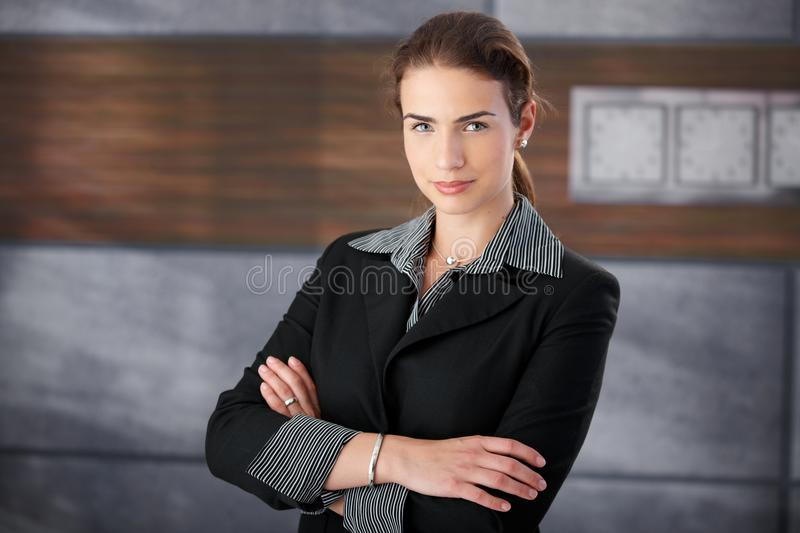 Well-dressed woman standing arms crossed in lobby stock photos