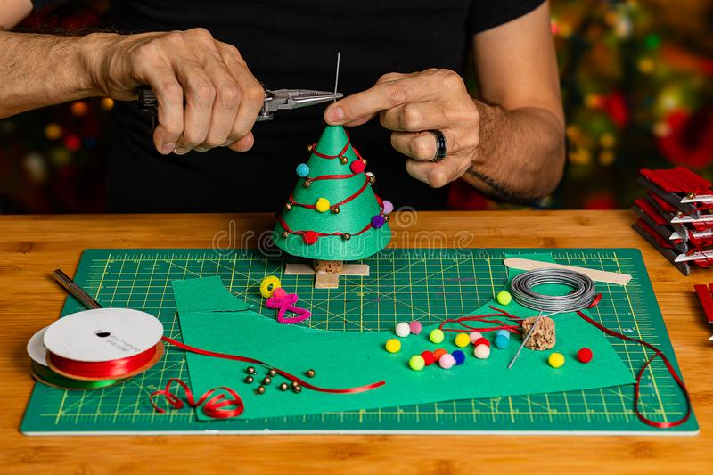 A well framed shot of a craftsman working on a craft Christmas scene. With construction paper, wire, ribbon, pom-poms, bells and pipe cleaners.  The background royalty free stock image