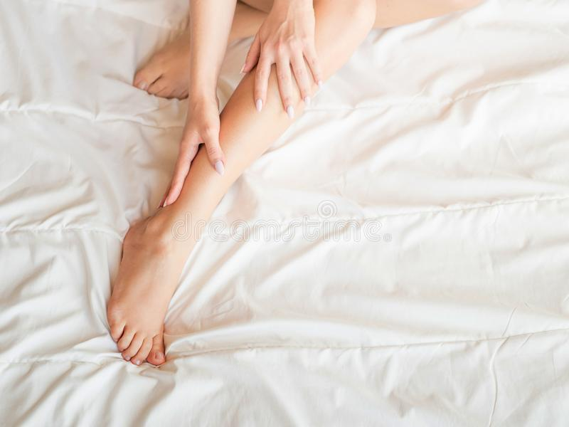 Well groomed female legs and hands, skincare concept, on white sheets. royalty free stock image