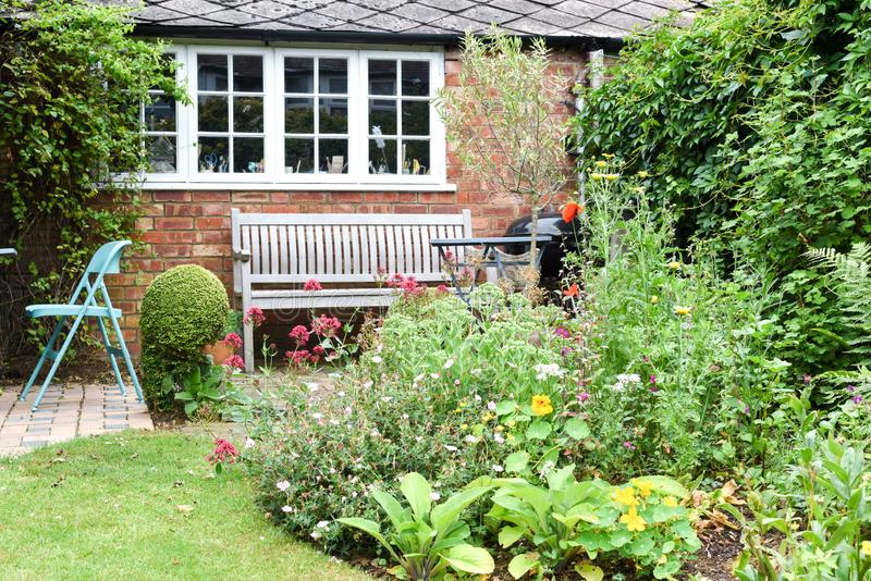 A well kept back yard or garden with lawn, flowers and seating area. On patio stock photography