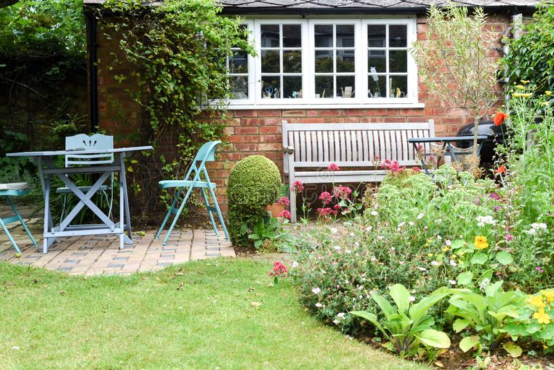 A well kept back yard or garden with lawn, flowers and seating area. On patio royalty free stock image