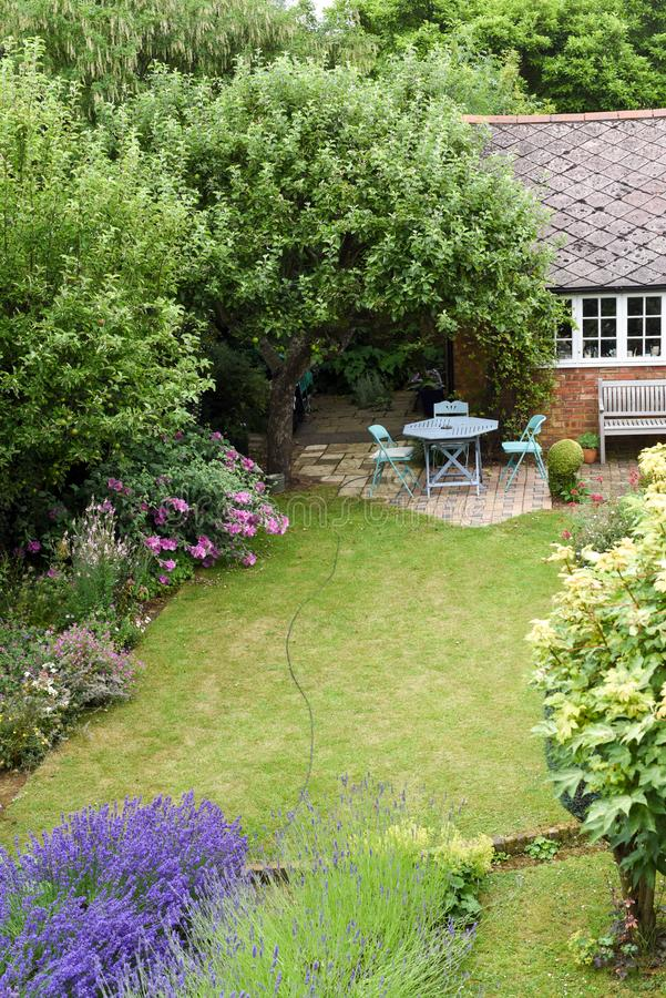 A well kept back yard or garden with lawn and seating area, high angle shot. Outside stock image
