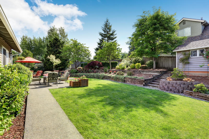 Well kept garden at backyard with concrete floor patio area. And opened red umbrella. Northwest, USA stock photo