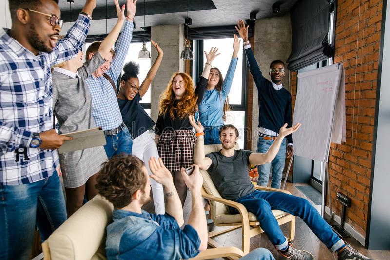 Well-knit organization of young perspective active people who are raising hands royalty free stock image