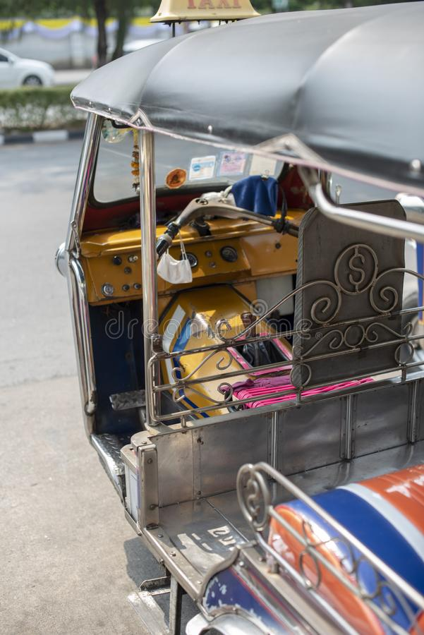 Well known and famous local taxi in Thailand, Tuk-Tuk, parking nearby tourist place, waiting for passengers asking for a ride. Image showing lots of details of royalty free stock photography