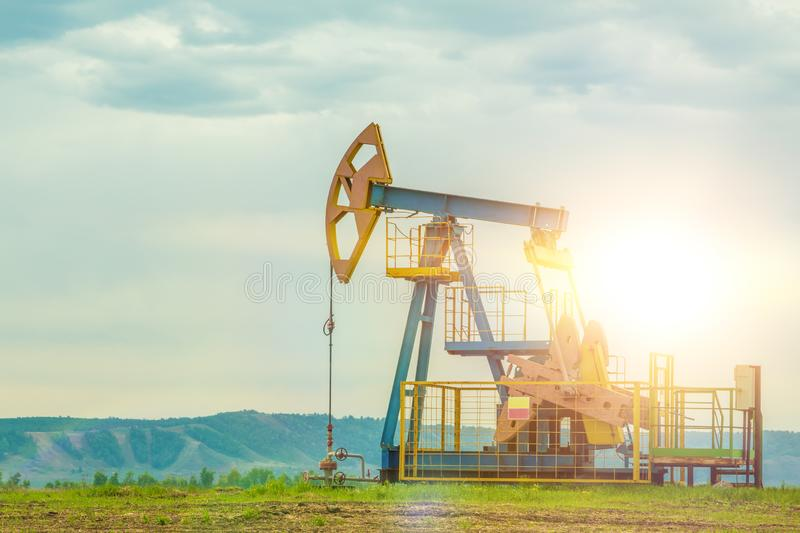 Well for oil production, drilling rig pump. Against the sky and the sun. Fuel, black gold, combustible, gasoline stock photography