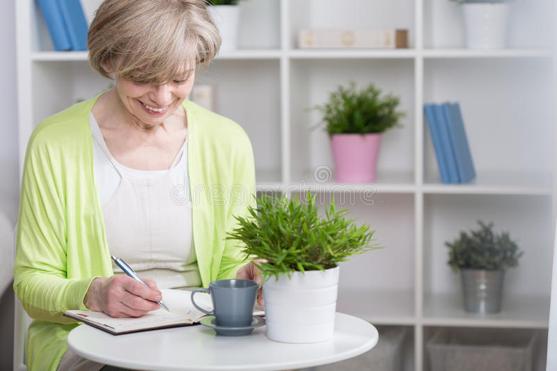 Well organized woman. Well organized senior woman with notebook, horizontal stock image