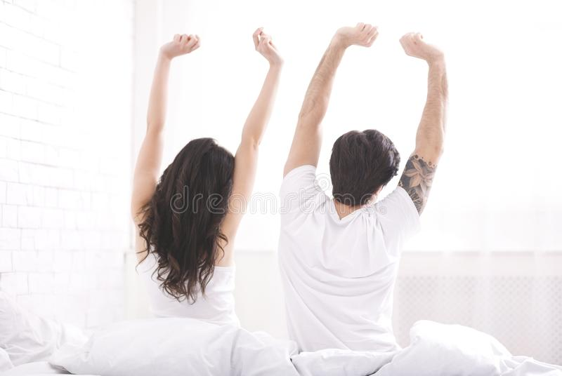 Well rested young couple stretching on bed in morning royalty free stock image