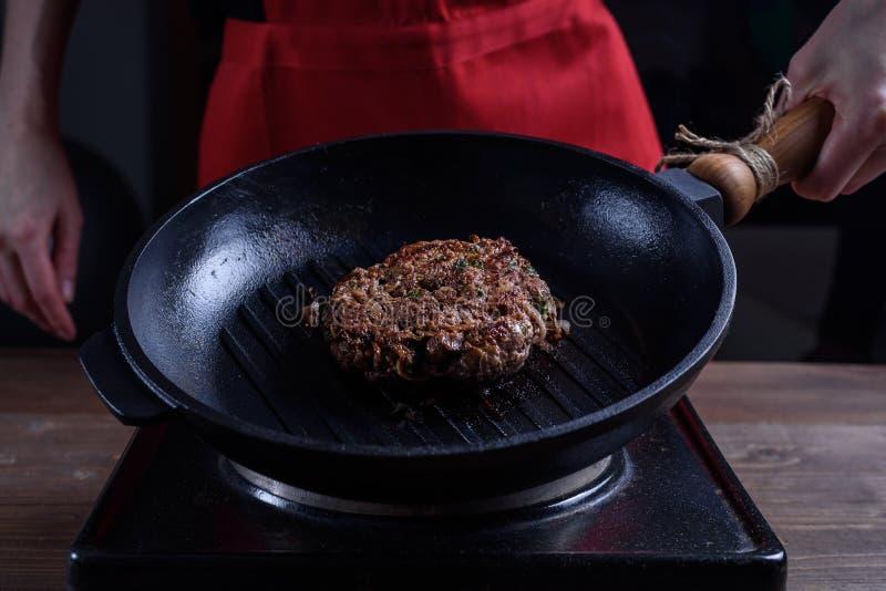Well robić piec kawałek wołowina na lanej żelaznej grill niecce w żeńskiej szefa kuchni ` s ręce zdjęcia stock