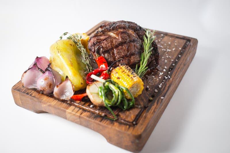 Well robić stek z piec na grillu warzywami na drewnianej desce obraz stock