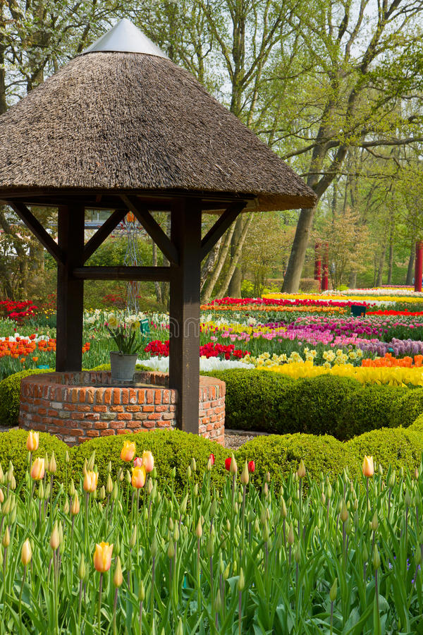 Well in spring garden stock photo